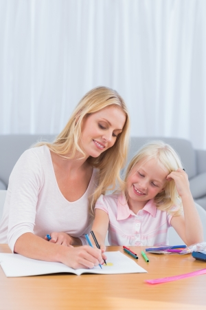 Smiling mother drawing with her daughter in the living room photo