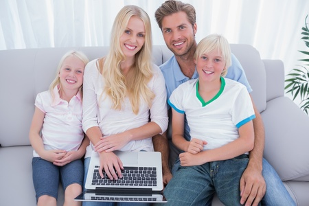 Cheerful family using laptop in the living room and looking at camera photo
