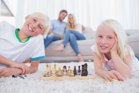 Children playing chess in front of their parents in the living room photo