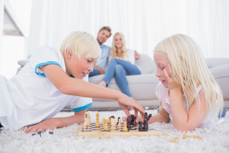 Brother and sister playing chess on the carpet photo