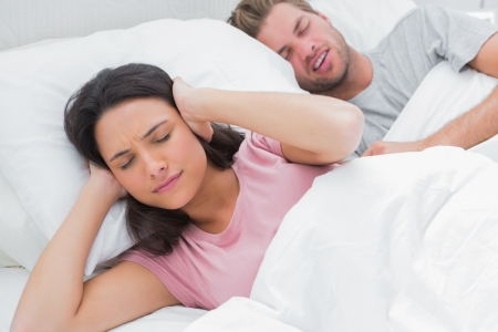 Woman covering ears while her husband is snoring next to her photo