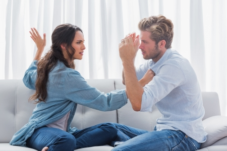 Upset woman about to slap her partner the living room photo