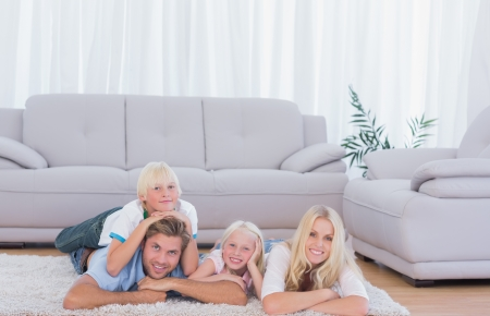 Family lying on the carpet and smiling at camera  photo