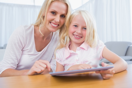 Mother and daughter using tablet pc together in the living room photo