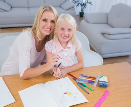 Mother and daughter drawing together in the living room and looking at camera photo