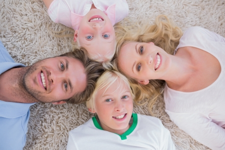 Overhead of family lying in a circle on carpet photo