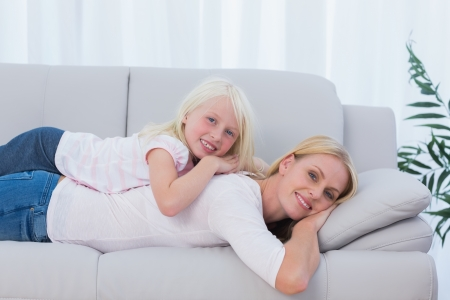 Smiling mother lying on couch with her daughter on her back photo