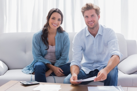 Happy couple doing their accounts sat in a couch Stock Photo - 20638516