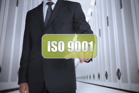 iso: Businessman in a data center selecting a green label with iso 9001 written on it