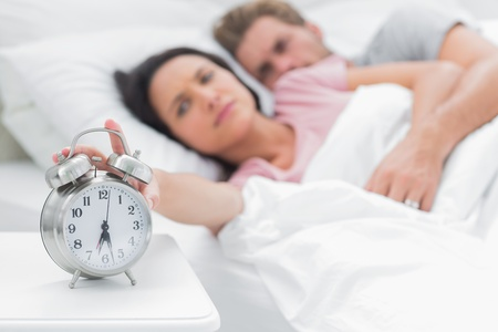 'bedside table': Attractive woman turning off the alarm clock on the bedside table Stock Photo