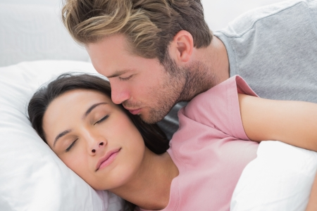 Man kissing his sleeping wife on the cheek in bed photo
