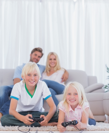 Children on the carpet playing video games in the living room Stock Photo - 20618487