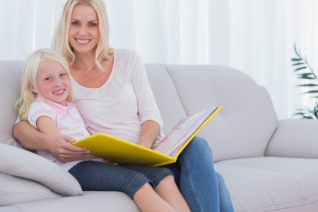 Mother and daughter sitting on couch reading a book and looking at camera photo