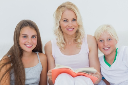 Portrait of mother holding a storybook to her happy children photo