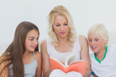 Mother reading a story to her happy children  photo