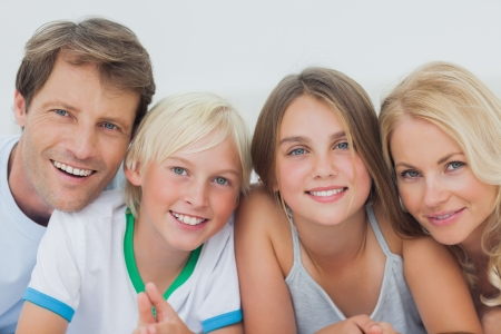cute blonde: Portrait of a cheerful family lying on the bed