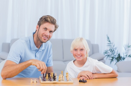 Little boy playing chess with his father in the living room photo