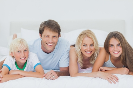 Parents and children lying on the bed and looking at camera photo