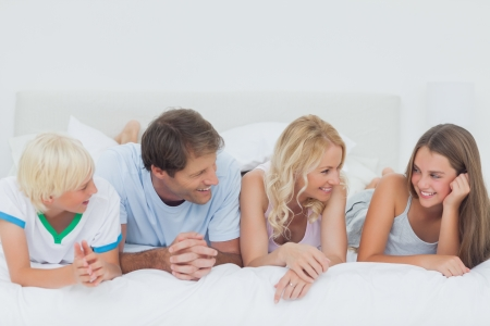 Cute family lying on the bed photo