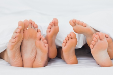 feet in bed: Feet of a family sticking out from the white quilt