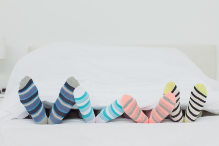 footsie: Familys feet in stripey socks at home in bed Stock Photo