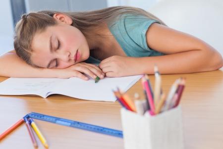agotado: Muchacha cansada que duerme en su tarea