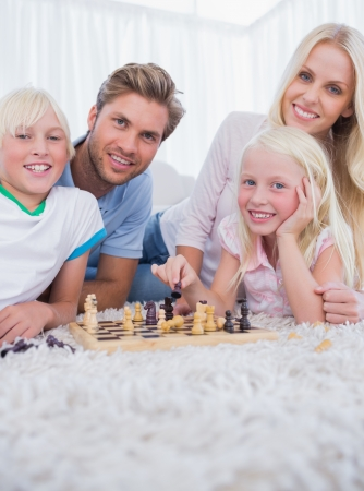 Family playing chess in the living room photo