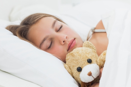 Cheerful girl sleeping with her teddy bear in her bed photo
