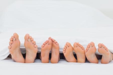 자신의 맨발을 보여주는 침대에 가족