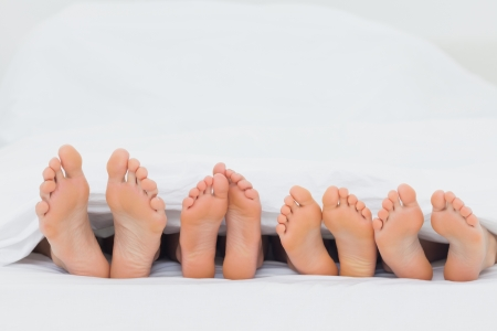 woman foot: Family on the bed showing their barefoot