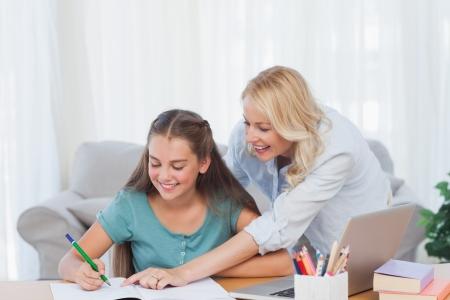 Mother pointing the book of her daughter during the homework