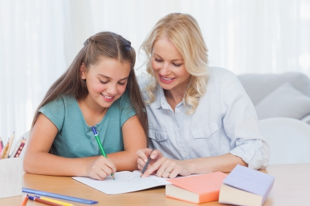Smiling mother helping daughter with homework in living room photo