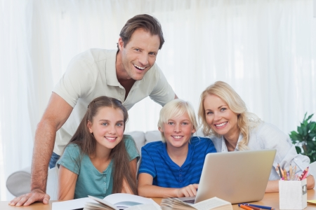 Smiling family using the laptop together to do homework in living room photo