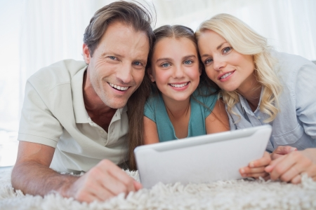 Portrait of a girl and her parents using a tablet lying on a carpet photo