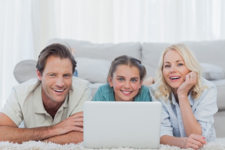 Cheerful parents and daughter using a laptop lying on a carpet photo