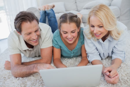 Happy parents and daughter using a laptop lying on a carpet photo