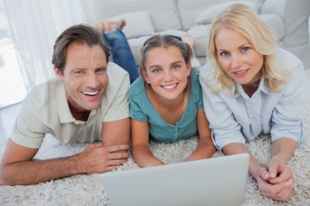 Portrait of parents and daughter using a laptop lying on a carpet photo