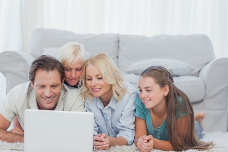 Beautiful family using a laptop lying on a carpet in the living room photo