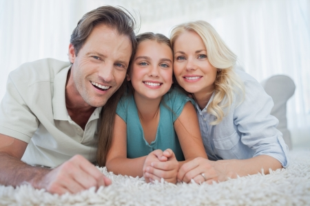 Portrait of a girl and her parents lying on a carpet in the living room photo