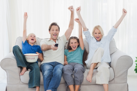 Family watching television and raising arms while holding pop corn photo