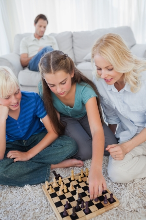 homely: Siblings and mother playing chess sitting on a carpet while father is sitting on a couch on the background