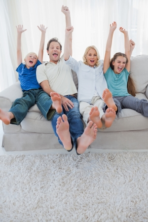 excited man: Portrait of a family watching television and raising arms sitting on a couch