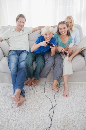 ni�os jugando videojuegos: Ni�os jugando videojuegos juntos sentados en el sof� mientras los padres est�n mirando Foto de archivo