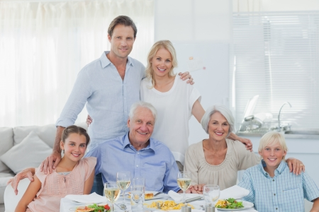 Extended family smiling at the dinner table in dining room photo