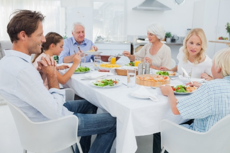 familia comiendo: Familia extensa en la mesa de la cena en la cocina Foto de archivo