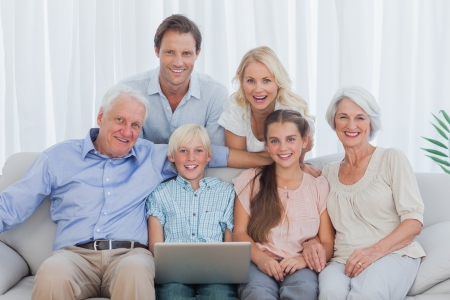 Extended family sitting on couch and using a laptop Stock Photo - 20639085