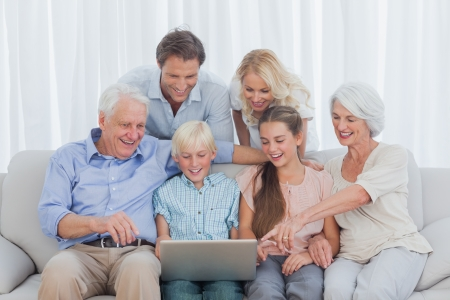 Extended family sitting on sofa and pointing the laptop Stock Photo - 20639089