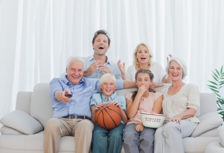 Extended family watching the television on couch Stock Photo - 20637350