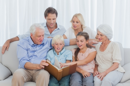 Extended family looking at a photo album in living room Stock Photo - 20638556
