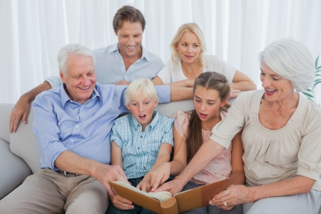 Extended family looking at their album photo in the living room Stock Photo - 20639210